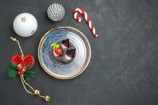 Vue de dessus délicieux cheesecake avec fraise et chocolat sur une plaque ovale jouets d'arbre de noël sur fond sombre isolé