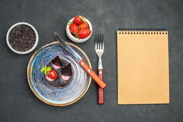 Vue de dessus délicieux cheesecake à la fraise et un couteau sur des bols à assiette avec des fraises sur fond sombre isolé