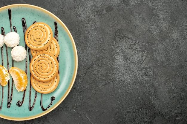 Vue de dessus de délicieux cookies avec des bonbons à la noix de coco et des fruits sur le bureau gris