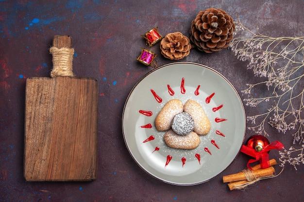 Vue de dessus de délicieux cookies avec des glaçages rouges sur fond noir