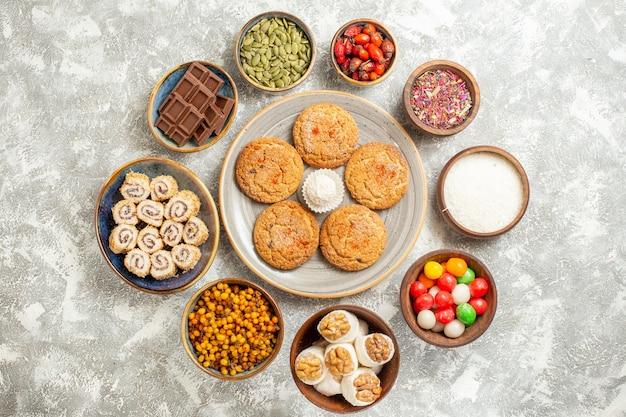 Vue de dessus de délicieux cookies avec de petits rouleaux sucrés sur fond blanc clair