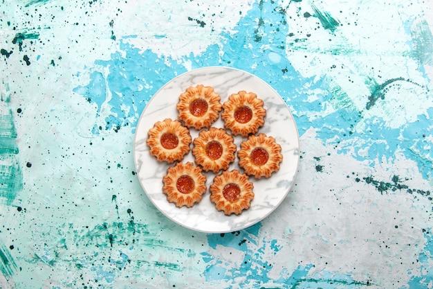 Vue de dessus de délicieux cookies rond formé avec de la confiture à l'intérieur de la plaque sur le fond bleu clair cookie sucre pâte à biscuits sucrée gâteau cuire