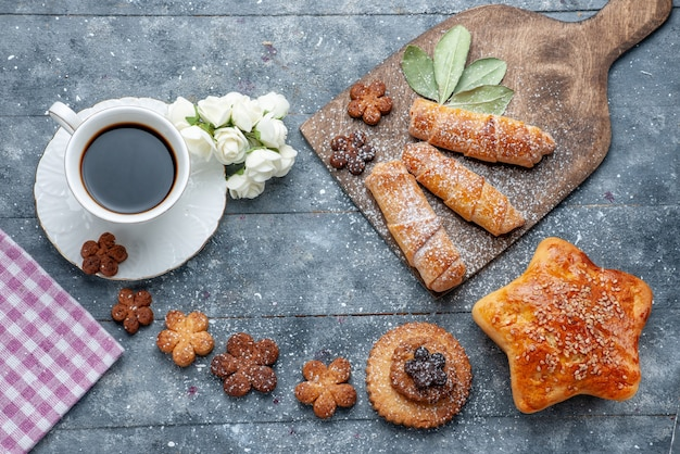 Vue de dessus de délicieux cookies sucrés avec une tasse de café et des bracelets sucrés
