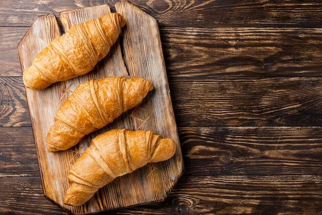 Vue de dessus de délicieux croissants au four sur planche de bois et espace copie