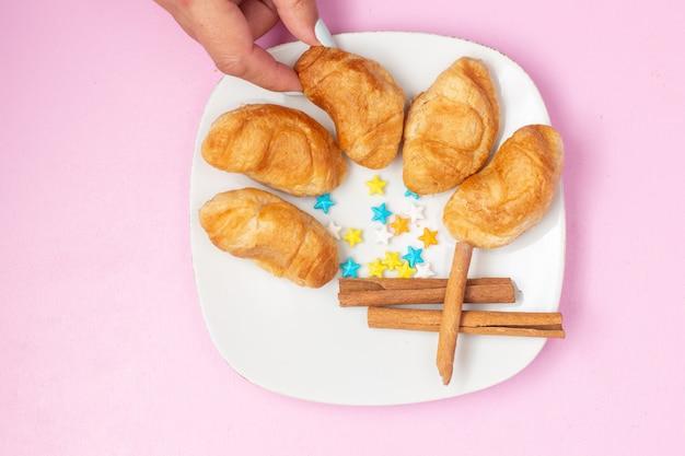 Vue de dessus de délicieux croissants cuits au four avec garniture de fruits à l'intérieur avec des bonbons à la cannelle sur le bureau rose