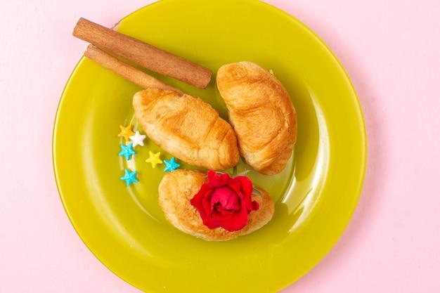 Vue de dessus de délicieux croissants cuits au four avec garniture de fruits à l'intérieur avec de la cannelle à l'intérieur de la plaque verte sur le fond rose