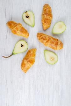 Une vue de dessus de délicieux croissants avec des poires fraîches sur le gâteau aux fruits de bureau blanc