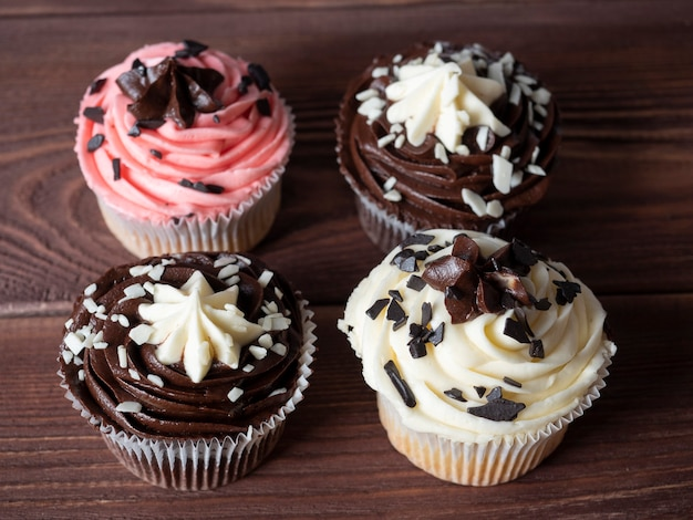 Vue de dessus de délicieux cupcakes au chocolat sucré allongé sur un fond en bois.