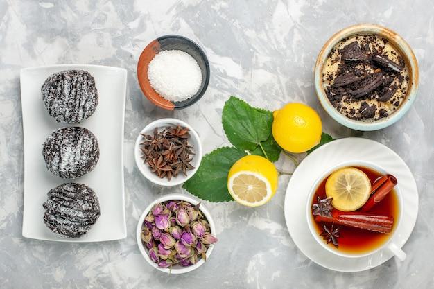 Vue de dessus délicieux dessert biscuit dessert crémeux avec tasse de thé et de citron sur la surface blanche biscuit aux fruits biscuit sucre gâteau sucré