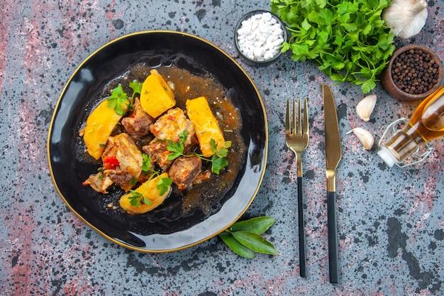 Vue de dessus d'un délicieux dîner avec pommes de terre à la viande servi avec du vert dans une assiette noire et des épices à l'ail bouteille d'huile tombée ensemble de couverts à fleurs et planche à découper