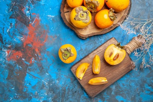 Vue de dessus de délicieux diospyros kaki entiers et coupés sur des planches à découper en bois marron