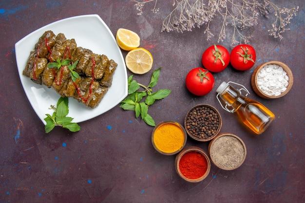 Vue de dessus de délicieux dolma de feuilles avec des assaisonnements au citron et des tomates sur le plat de fond sombre feuille alimentaire dîner de viande