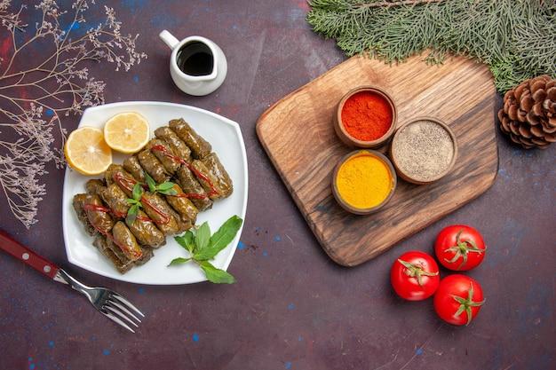 Vue de dessus de délicieux dolma de feuilles avec des tranches de citron et des assaisonnements sur fond sombre plat de repas feuille de dîner