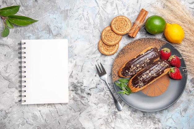 Vue de dessus de délicieux éclairs au chocolat avec des biscuits sur un biscuit de dessert au gâteau de table blanc