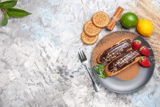 Vue de dessus de délicieux éclairs au chocolat avec des biscuits sur un biscuit de gâteau de dessert de table légère