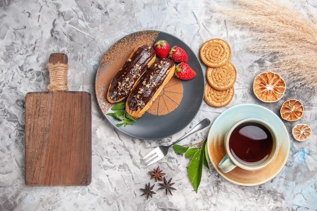 Vue de dessus de délicieux éclairs au chocolat avec du thé sur un biscuit de gâteau au dessert au sol blanc