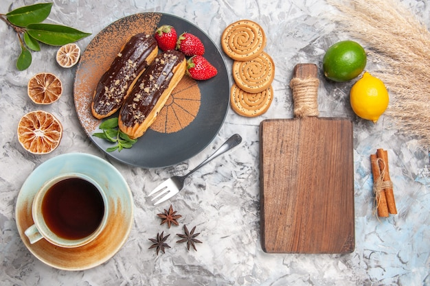 Vue de dessus de délicieux éclairs au chocolat avec du thé sur un biscuit de gâteau de dessert de bureau blanc