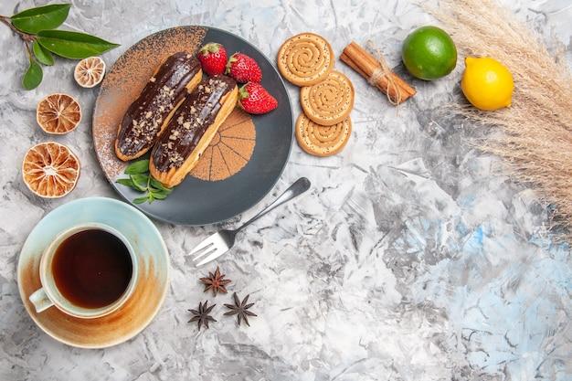 Vue de dessus de délicieux éclairs au chocolat avec du thé sur le biscuit de gâteau de dessert de table blanche