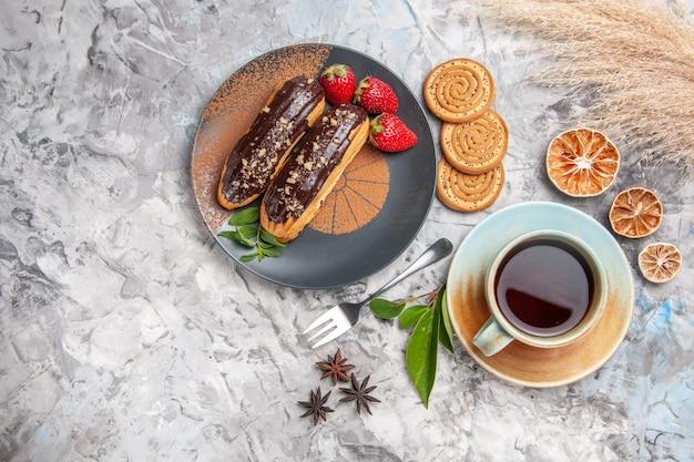 Vue de dessus de délicieux éclairs au chocolat avec du thé sur des biscuits de gâteau de dessert de table blanche