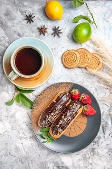 Vue de dessus de délicieux éclairs au chocolat avec du thé sur un gâteau de dessert aux biscuits de table blanc clair