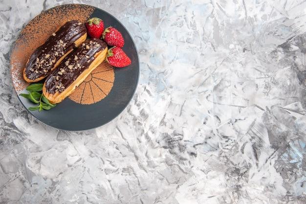 Vue de dessus de délicieux éclairs au chocolat avec des fraises sur un biscuit de biscuit de dessert de bureau léger