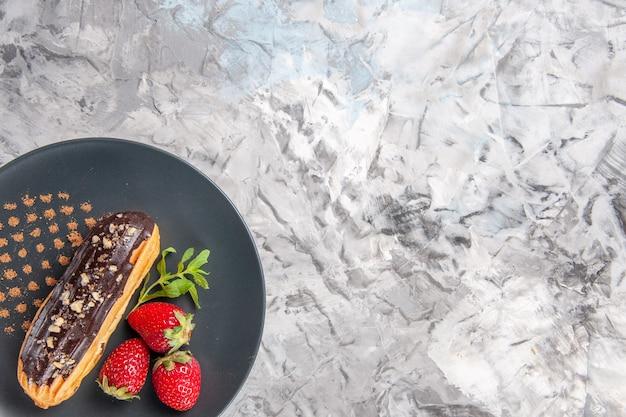 Vue de dessus de délicieux éclairs au chocolat avec des fraises sur des fruits de gâteau de dessert au sol léger