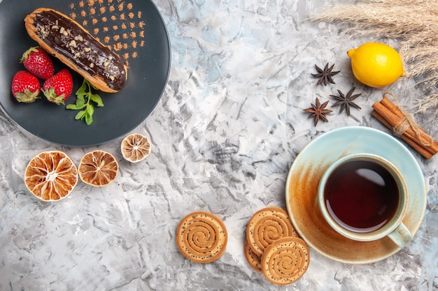 Vue de dessus de délicieux éclairs au chocolat avec une tasse de thé sur un dessert aux biscuits légers