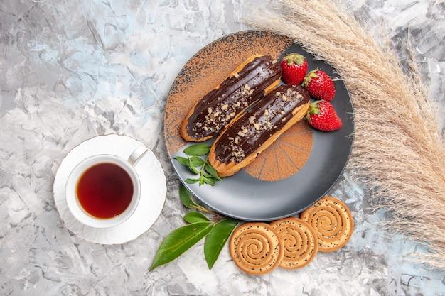 Vue de dessus de délicieux éclairs au chocolat avec une tasse de thé sur le dessert biscuit de gâteau de table blanc