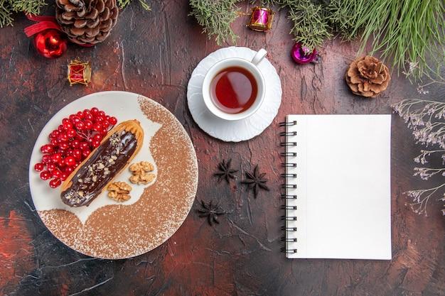 Vue de dessus de délicieux éclairs de choco avec des baies et du thé sur la tarte au gâteau au sol sombre dessert sucré