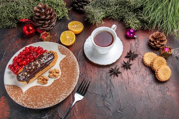 Vue de dessus de délicieux éclairs de choco avec des baies et du thé sur la tarte au gâteau de table sombre dessert sucré