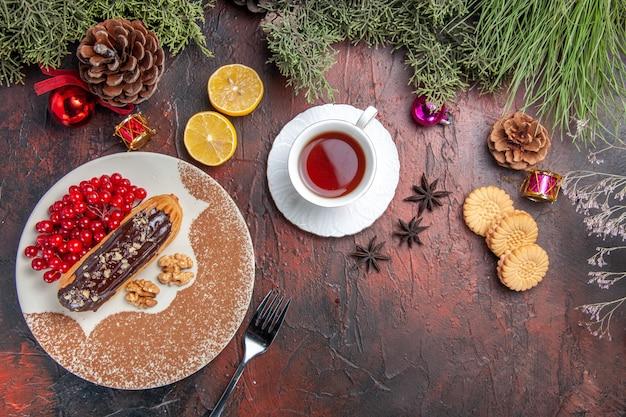 Vue de dessus de délicieux éclairs choco avec des baies et du thé sur des tartes au gâteau de table sombre dessert sucré
