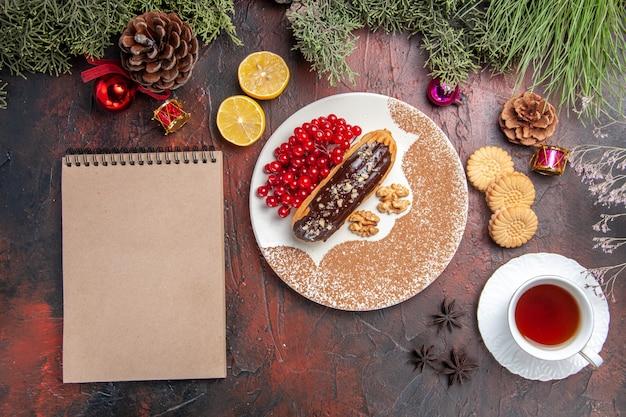 Vue de dessus de délicieux éclairs de choco avec du thé et des baies sur la table sombre dessert gâteau sucré tarte