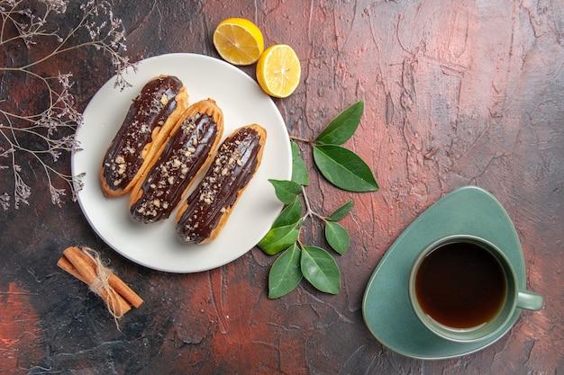 Vue de dessus de délicieux éclairs de choco à l'intérieur de la plaque sur la tarte au gâteau de table sombre dessert sucré