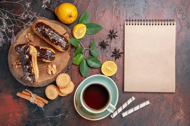 Vue de dessus de délicieux éclairs de choco avec une tasse de thé sur le gâteau de bonbons dessert table sombre