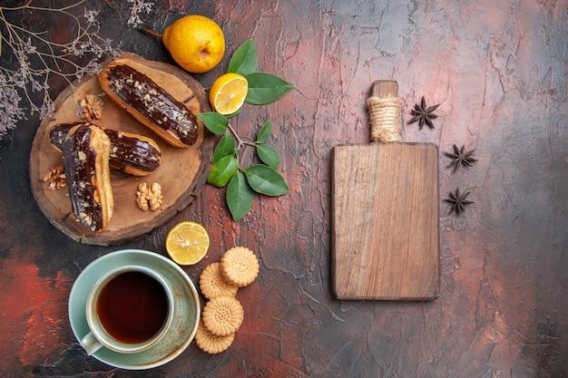 Vue de dessus de délicieux éclairs de choco avec une tasse de thé sur le gâteau sucré dessert table sombre