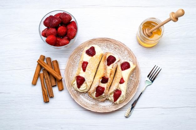 Une vue de dessus de délicieux éclairs avec de la crème et des fraises avec de la cannelle et du miel sur les fruits du gâteau fond blanc