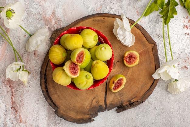 Vue de dessus de délicieux fœtus de figues douces fraîches à l'intérieur de la plaque rouge avec des fleurs sur un bureau blanc