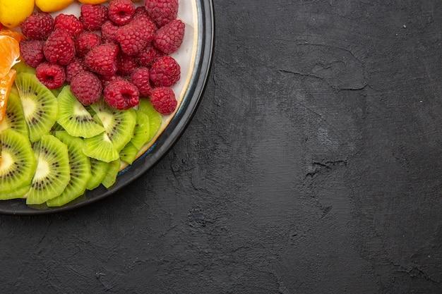 Vue de dessus de délicieux fruits tranchés à l'intérieur de la plaque sur un arbre fruitier tropical sombre régime alimentaire mûr exotique photo espace libre