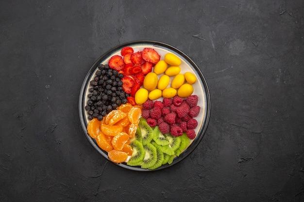 Vue de dessus de délicieux fruits tranchés à l'intérieur de la plaque sur une photo de régime mûr exotique de fruits tropicaux foncés