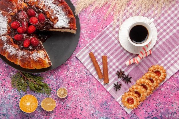 Vue de dessus délicieux gâteau au chocolat avec des biscuits et une tasse de thé sur le biscuit de bureau rose clair