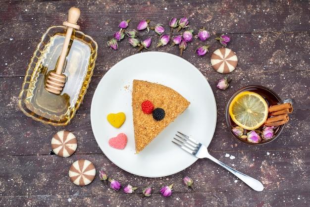 Une vue de dessus délicieux gâteau au miel avec des bonbons au miel et des fleurs sur le fond sombre gâteau au thé bonbons