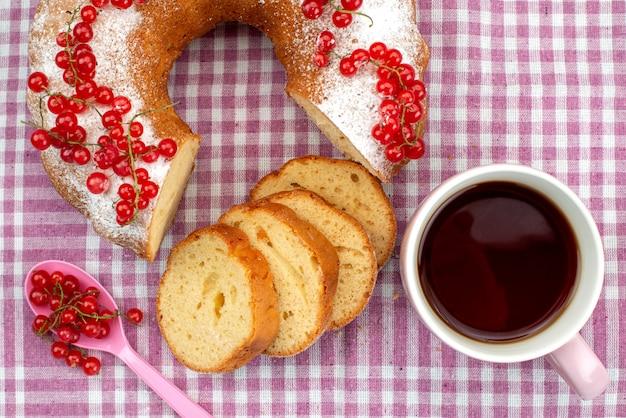 Une vue de dessus délicieux gâteau aux canneberges rouges fraîches, cannelle et thé sur le gâteau de tissu violet biscuit thé berry sucre