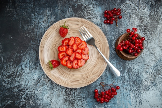 Vue de dessus délicieux gâteau aux fraises avec des baies sur un bureau sombre