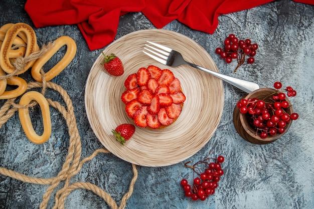 Vue de dessus délicieux gâteau aux fraises avec des baies sur fond sombre