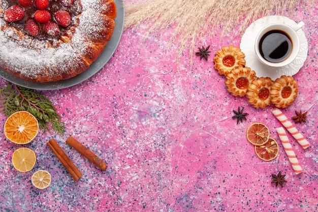 Vue de dessus délicieux gâteau aux fraises avec des biscuits et une tasse de thé sur le gâteau de fond rose cuire la tarte aux biscuits biscuits au sucre sucré