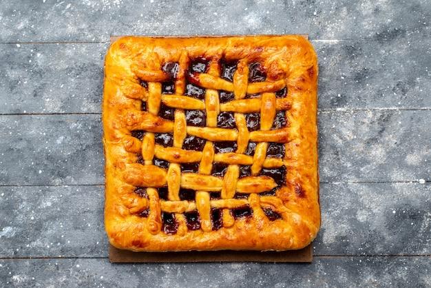 Une vue de dessus délicieux gâteau aux fraises cuit avec de la gelée de fraises sur le bureau gris gâteau biscuit thé fruits