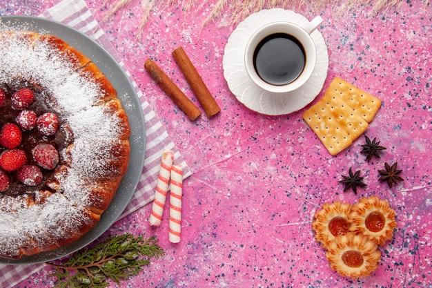 Vue de dessus délicieux gâteau aux fraises avec une tasse de craquelins au thé et sur une surface rose