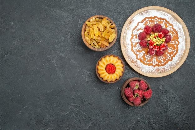 Vue de dessus délicieux gâteau aux framboises avec des raisins secs sur une surface grise gâteau au sucre biscuit au thé tarte sucrée