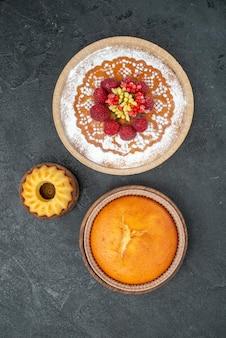 Vue de dessus délicieux gâteau aux framboises et tarte ronde sur fond gris gâteau tarte aux fruits biscuit sucré