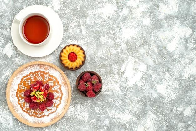 Vue de dessus délicieux gâteau aux framboises avec une tasse de thé sur une surface blanche biscuit thé sucré tarte gâteau sucre